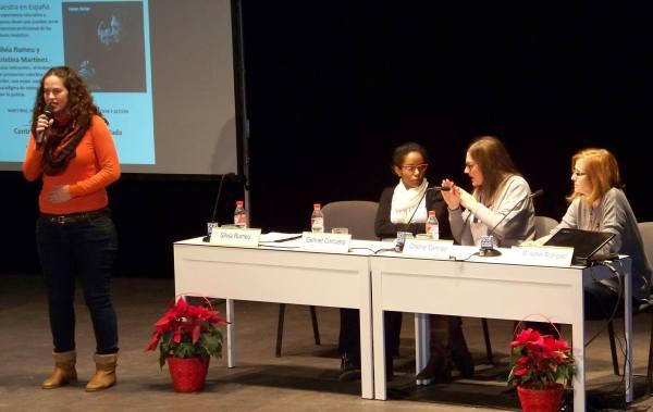 Silvia está de pie dando la conferencia y Genet y Cristina están a su lado interpretándola. La moderadora del acto está en la mesa junto a ellas